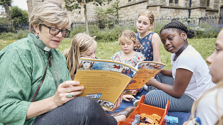 Vicar reading a book with a group of children