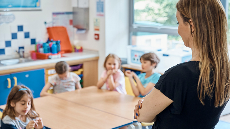 Primary school teachers supervises toddlers from front of classroom