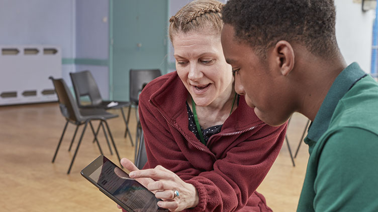 Adult shows young volunteer information on tablet