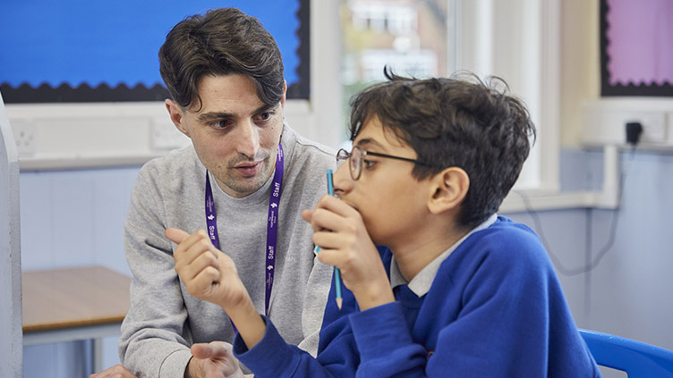 Teaching assistant supports pupil during his maths lesson