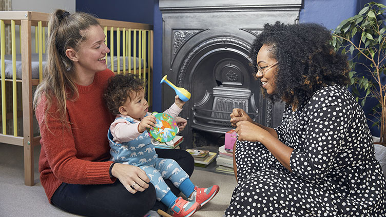 Volunteer engages with parent and infant in their home
